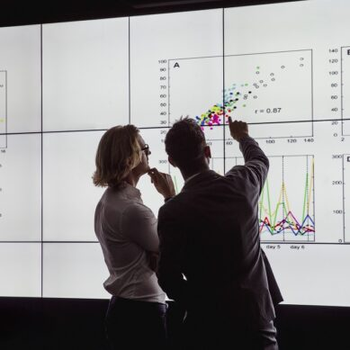 Business men in a dark room standing in front of a large data display