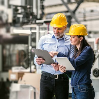 An industrial man and woman engineers with tablet in a factory checking documents.